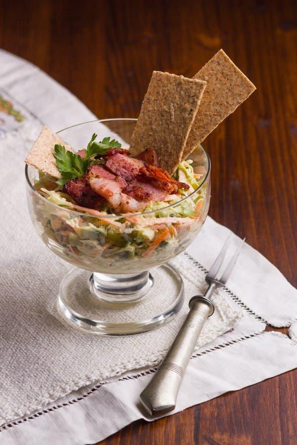 De vitaminesalade van geraspte wortel en kool in witte die onderdompeling wordt gemaakt, met gebakken, knapperig bacon wordt beha stock afbeelding
