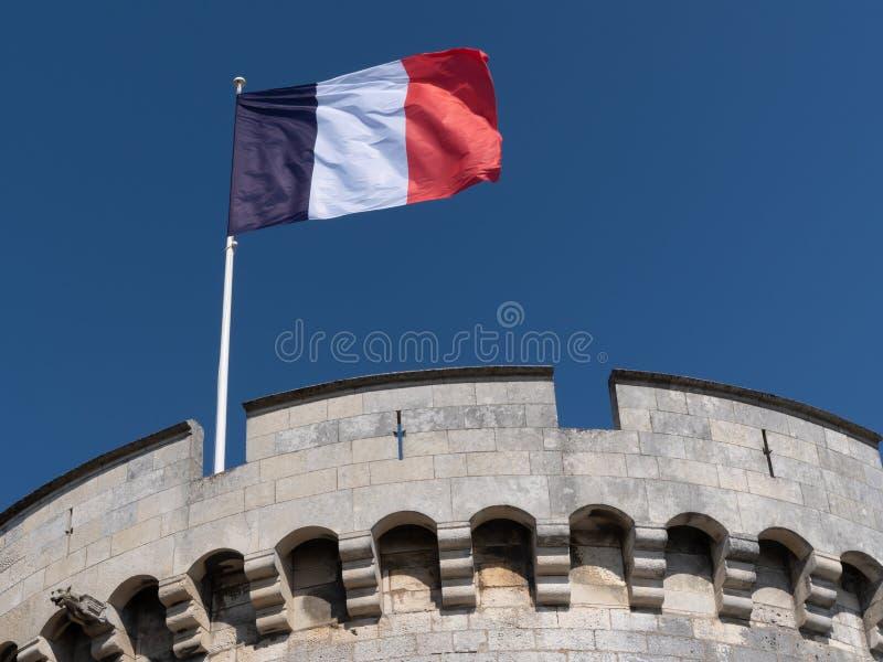 De vlag die van Frankrijk tegen schone blauwe hemel bij La Rochelle Tower golven royalty-vrije stock foto's