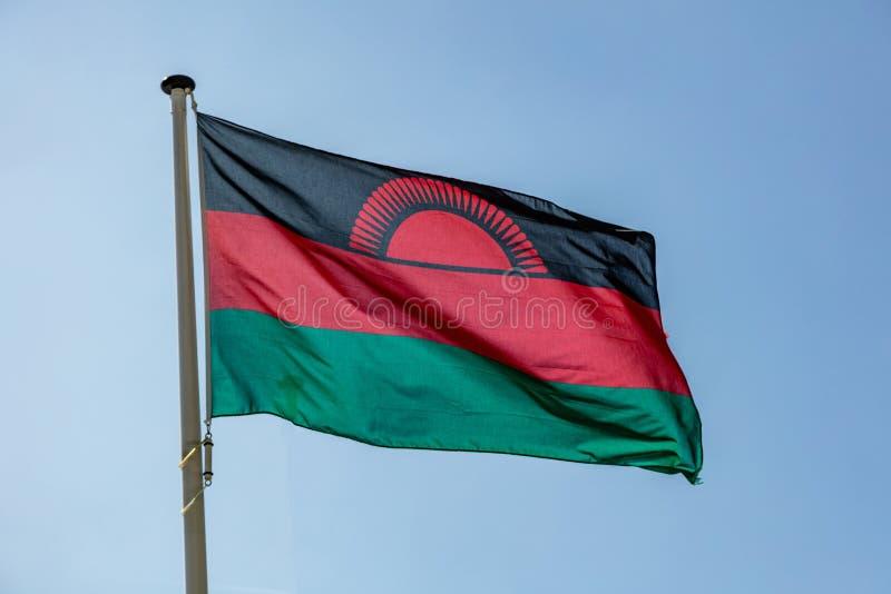 De vlag die van Malawi tegen duidelijke blauwe hemel golven stock afbeeldingen