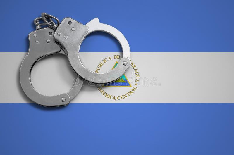 De vlag en de politiehandcuffs van Nicaragua Het concept misdaad en inbreuken in het land stock foto's