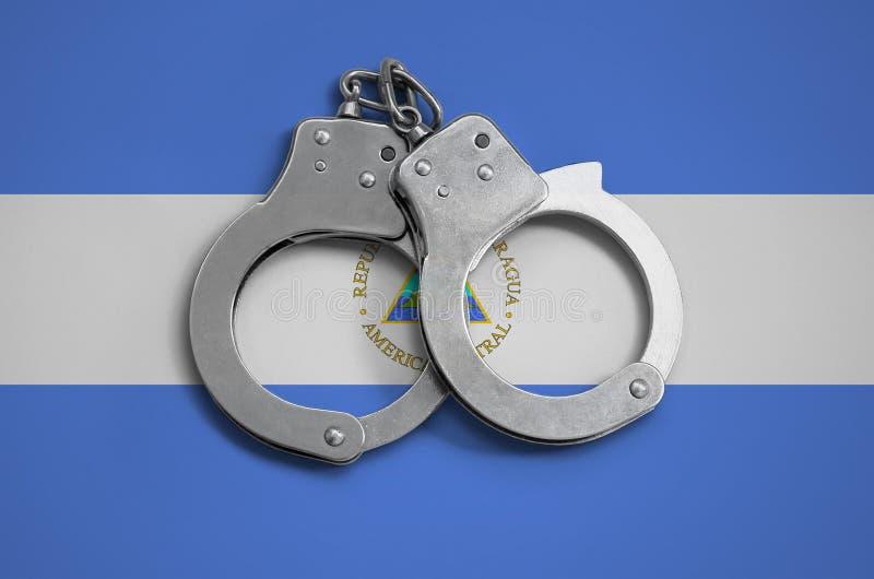 De vlag en de politiehandcuffs van Nicaragua Het concept naleving van de wet in het land en bescherming tegen misdaad stock foto's
