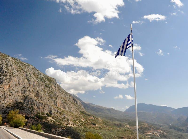 De vlag en de weg van Griekenland in bergen aan Delfi stock foto's