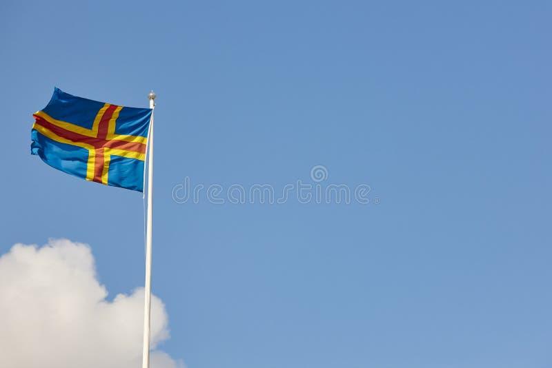 De vlag van Alandeilanden over een blauwe hemel De achtergrond van Finland royalty-vrije stock afbeeldingen