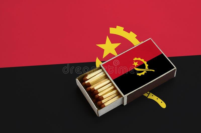 De vlag van Angola wordt getoond in een open lucifersdoosje, dat met gelijken wordt gevuld en op een grote vlag ligt royalty-vrije illustratie