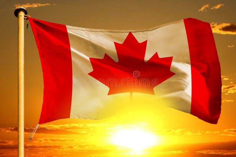 De vlag van Canada het weven op de mooie oranje zonsondergang met wolkenachtergrond stock fotografie