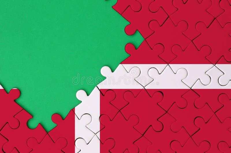 De vlag van Denemarken wordt afgeschilderd op een voltooide puzzel met vrije groene exemplaarruimte op de linkerkant stock afbeeldingen