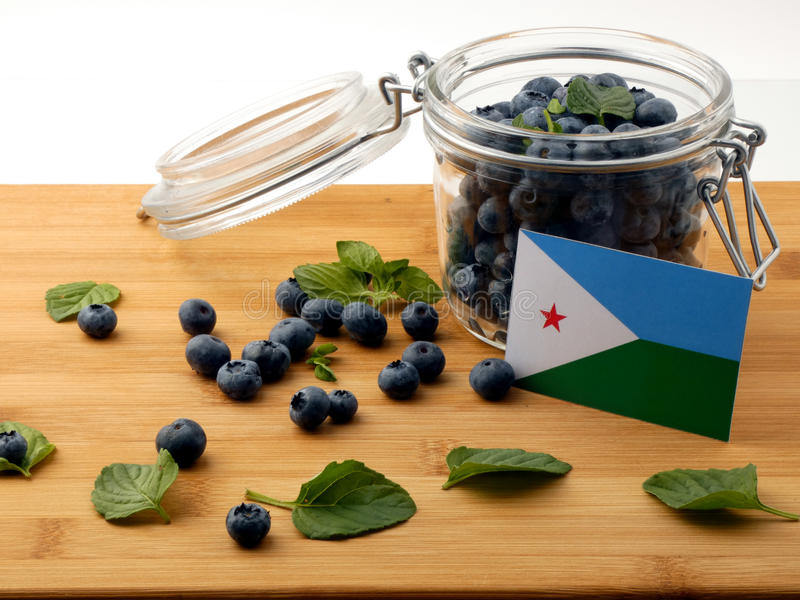 De vlag van Djibouti op een houten plank met bosbessen op whi royalty-vrije stock foto's
