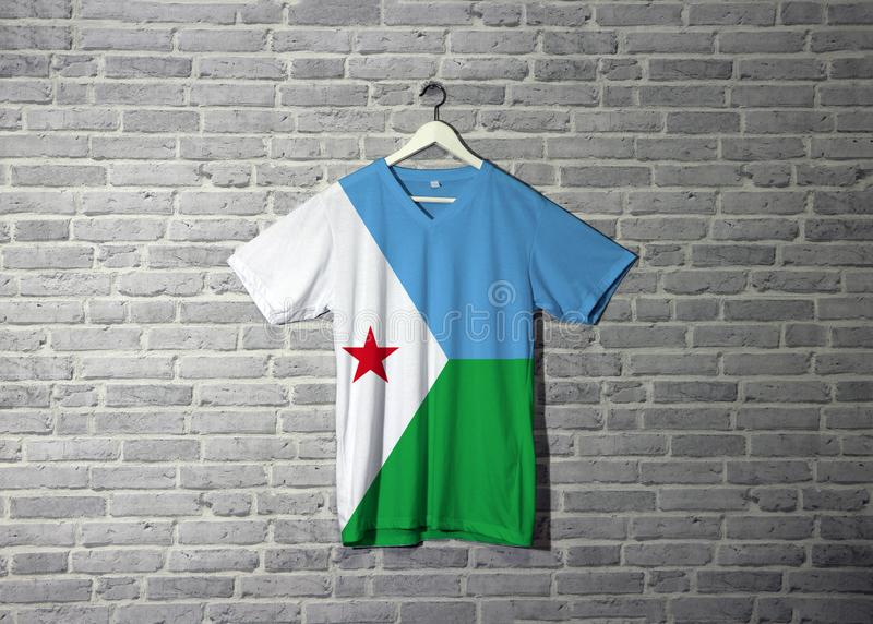 De vlag van Djibouti op overhemd en het hangen op de muur met het behang van het baksteenpatroon royalty-vrije stock fotografie