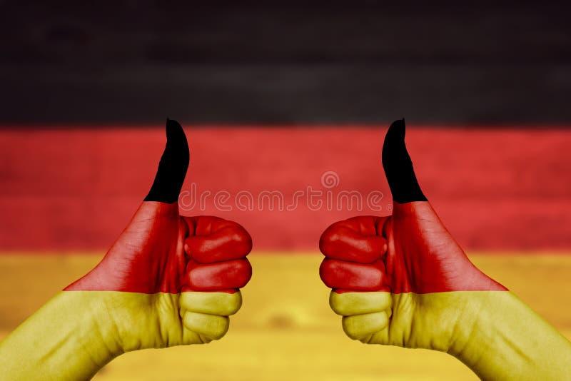 De vlag van Duitsland op vrouwelijke handen wordt geschilderd die beduimelt omhoog stock foto's