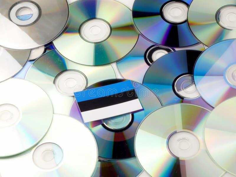 De vlag van Estland bovenop CD en DVD-stapel op wit wordt geïsoleerd dat stock afbeeldingen