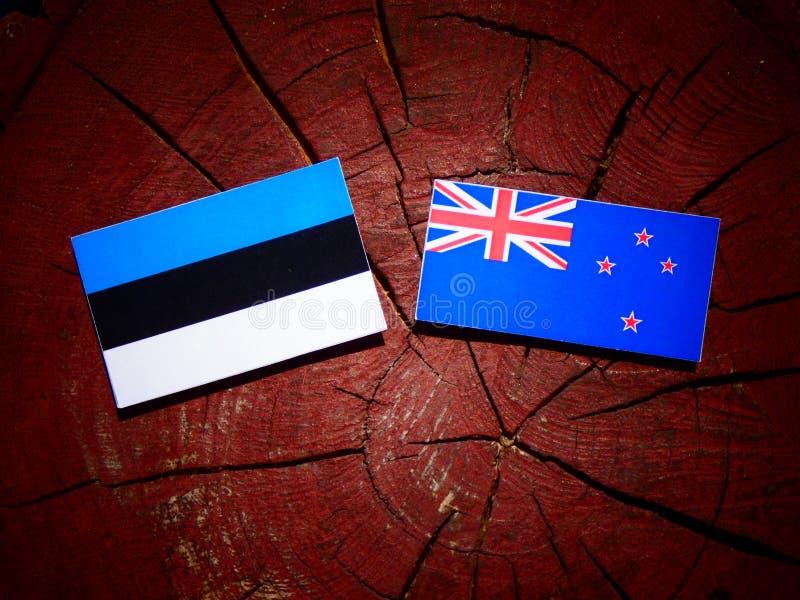 De vlag van Estland met de vlag van Nieuw Zeeland op een geïsoleerde boomstomp stock fotografie