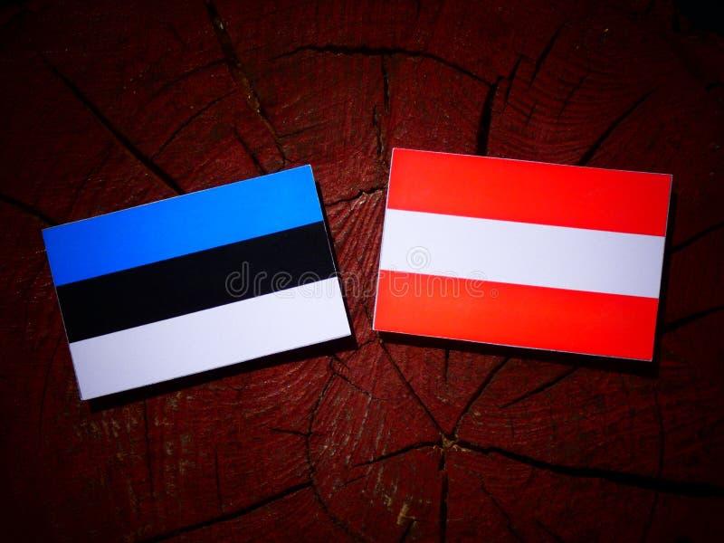 De vlag van Estland met Oostenrijkse vlag op een boomstomp stock afbeeldingen
