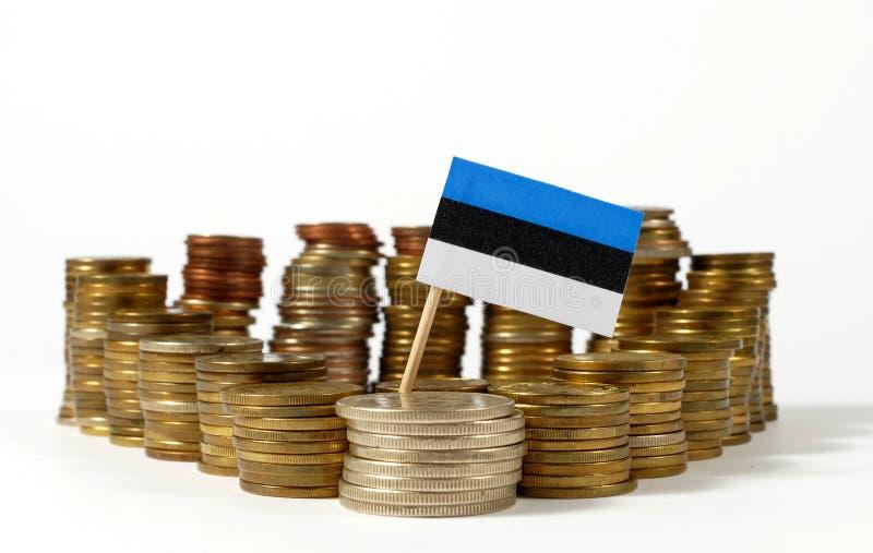 De vlag van Estland met stapel geldmuntstukken stock afbeeldingen