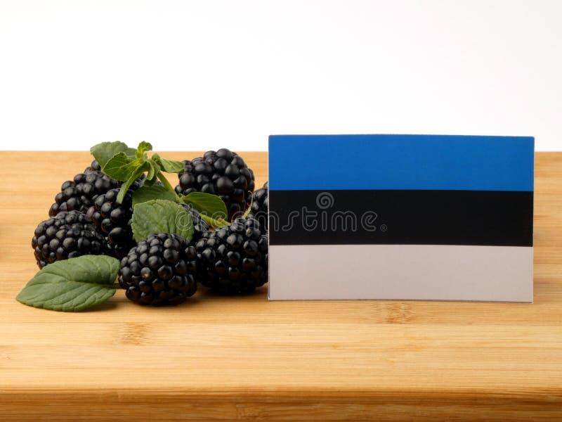 De vlag van Estland op een houten die paneel met braambessen op w wordt geïsoleerd royalty-vrije stock fotografie