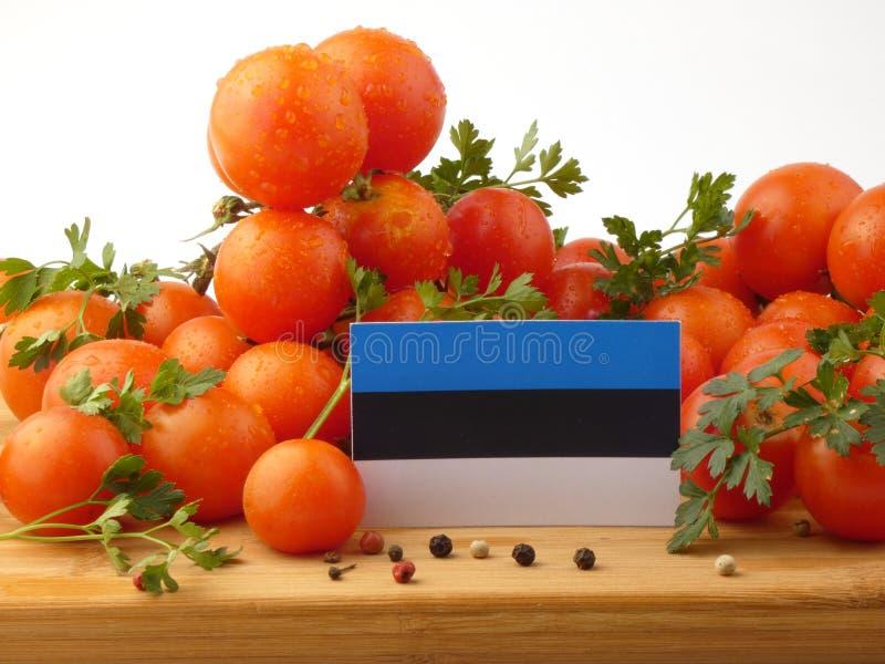 De vlag van Estland op een houten die paneel met tomaten op een wit wordt geïsoleerd stock foto's