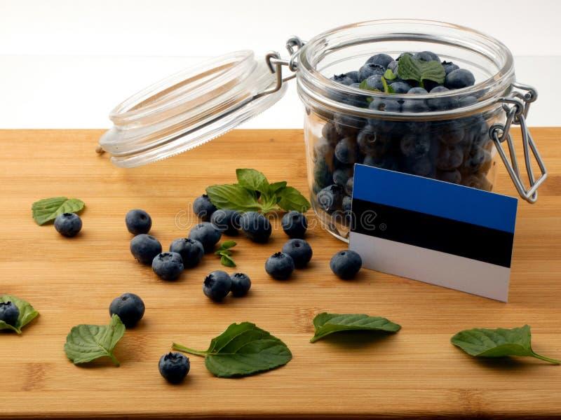De vlag van Estland op een houten plank met bosbessen op whit stock foto's