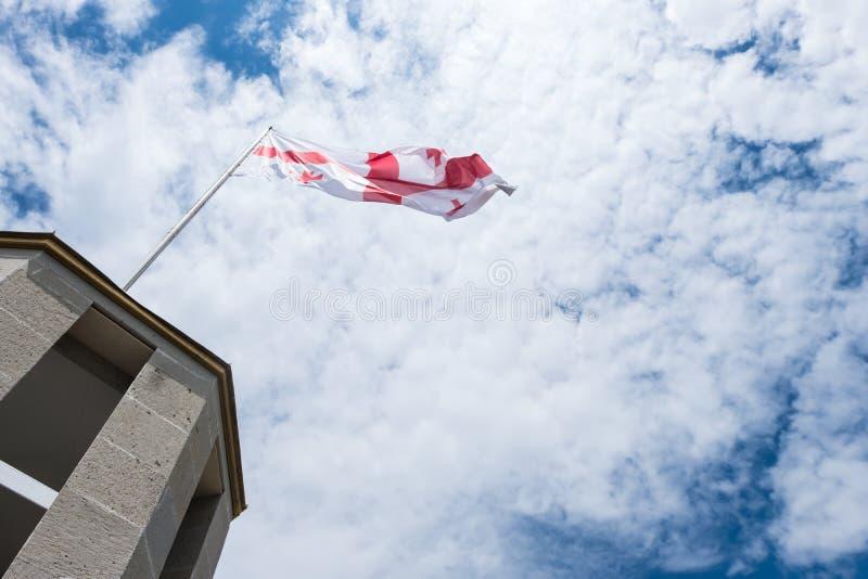 De vlag van Georgië met blauwe hemel en wolken royalty-vrije stock foto