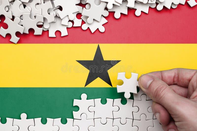De vlag van Ghana wordt afgeschilderd op een lijst waarop de menselijke hand een raadsel van witte kleur vouwt stock afbeelding