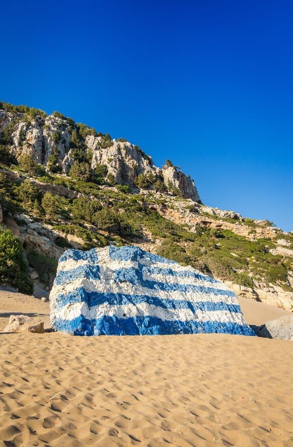 De vlag van Griekenland op Tsambika-strandrots die wordt geschilderd stock afbeeldingen