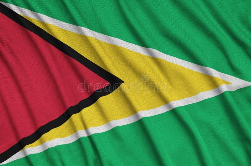 De vlag van Guyana wordt afgeschilderd op een stof van de sportendoek met vele vouwen De banner van het sportteam stock afbeelding