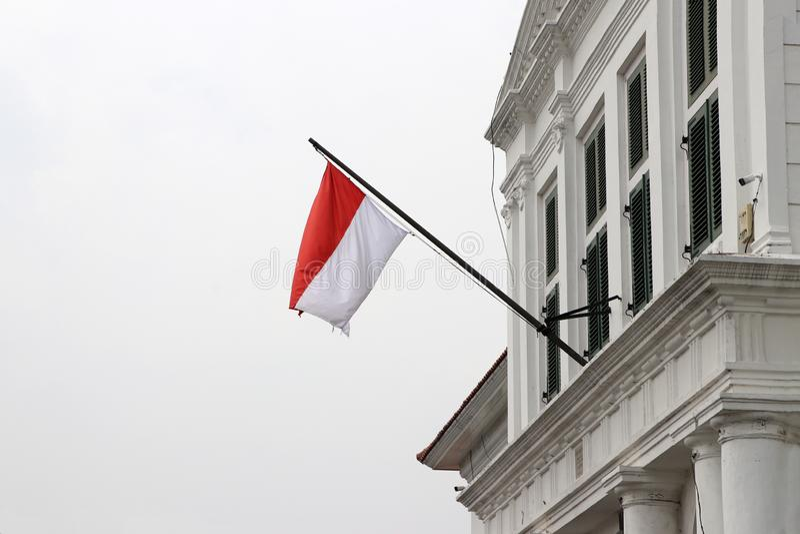 De vlag van Indonesië op de de bouw slag door de wind stock fotografie