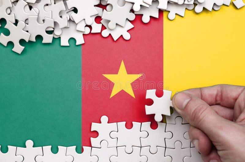 De vlag van Kameroen wordt afgeschilderd op een lijst waarop de menselijke hand een raadsel van witte kleur vouwt royalty-vrije stock afbeeldingen