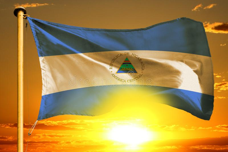 De vlag van Nicaragua het weven op de mooie oranje zonsondergang met wolkenachtergrond stock fotografie