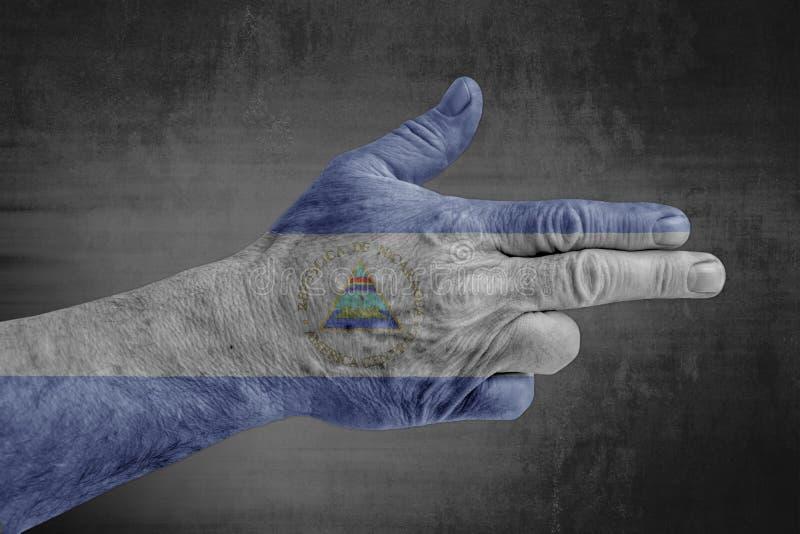 De vlag van Nicaragua op mannelijke hand zoals een kanon wordt geschilderd dat royalty-vrije stock afbeelding