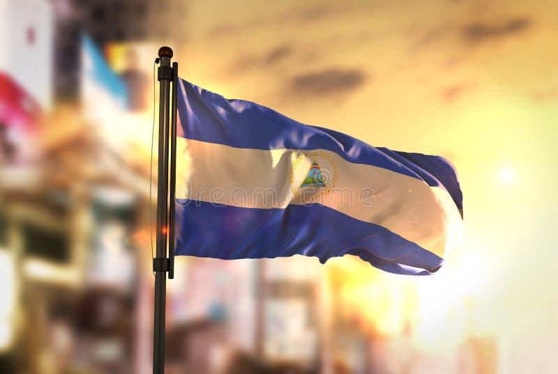 De Vlag van Nicaragua tegen Stad Vage Achtergrond bij Zonsopgang Backli stock afbeeldingen