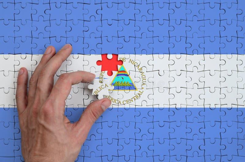 De vlag van Nicaragua wordt afgeschilderd op een raadsel, dat de mensen` s hand om voltooit te vouwen royalty-vrije stock afbeelding