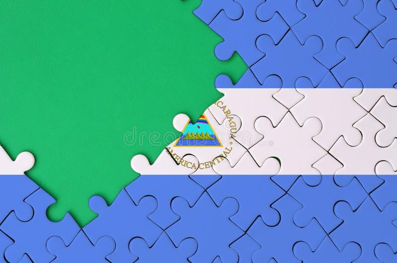 De vlag van Nicaragua wordt afgeschilderd op een voltooide puzzel met vrije groene exemplaarruimte op de linkerkant royalty-vrije stock foto