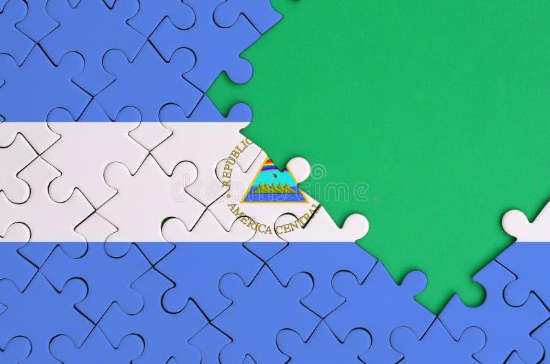 De vlag van Nicaragua wordt afgeschilderd op een voltooide puzzel met vrije groene exemplaarruimte op de rechterkant stock fotografie