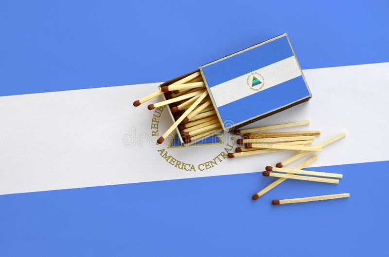 De vlag van Nicaragua wordt getoond op een open lucifersdoosje, waarvan verscheidene gelijken vallen en op een grote vlag ligt stock afbeeldingen