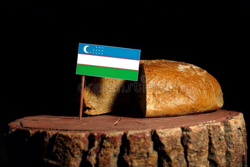 De vlag van Oezbekistan op een stomp met brood stock fotografie