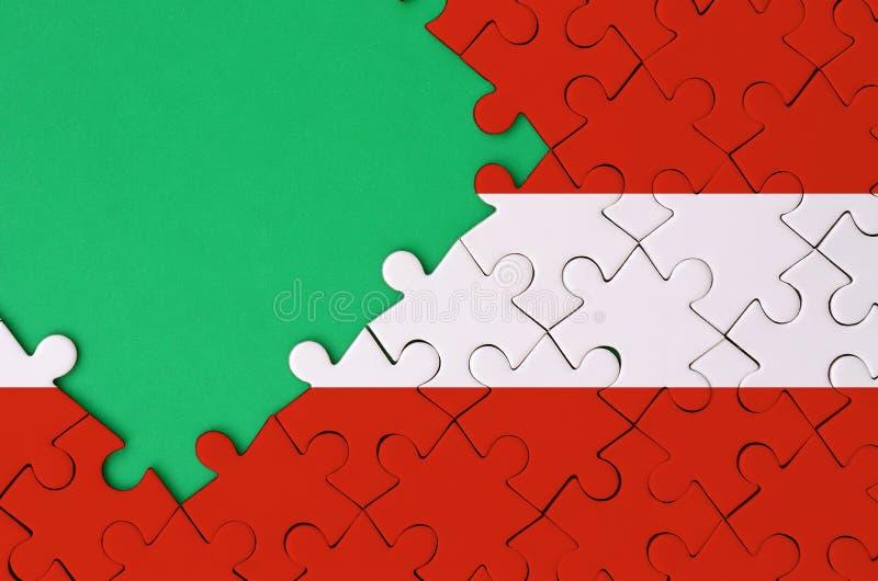 De vlag van Oostenrijk wordt afgeschilderd op een voltooide puzzel met vrije groene exemplaarruimte op de linkerkant stock foto's