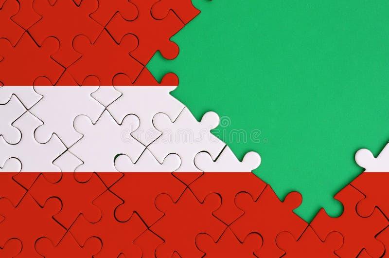 De vlag van Oostenrijk wordt afgeschilderd op een voltooide puzzel met vrije groene exemplaarruimte op de rechterkant royalty-vrije illustratie