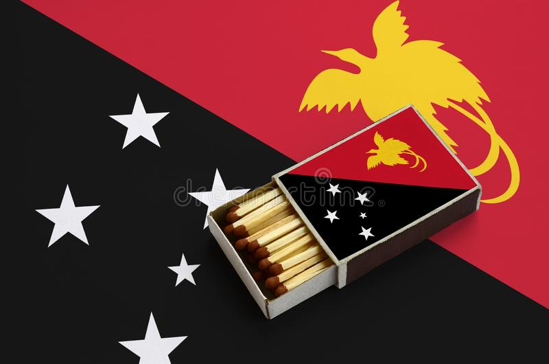 De vlag van Papoea-Nieuw-Guinea wordt getoond in een open lucifersdoosje, dat met gelijken wordt gevuld en op een grote vlag ligt stock illustratie