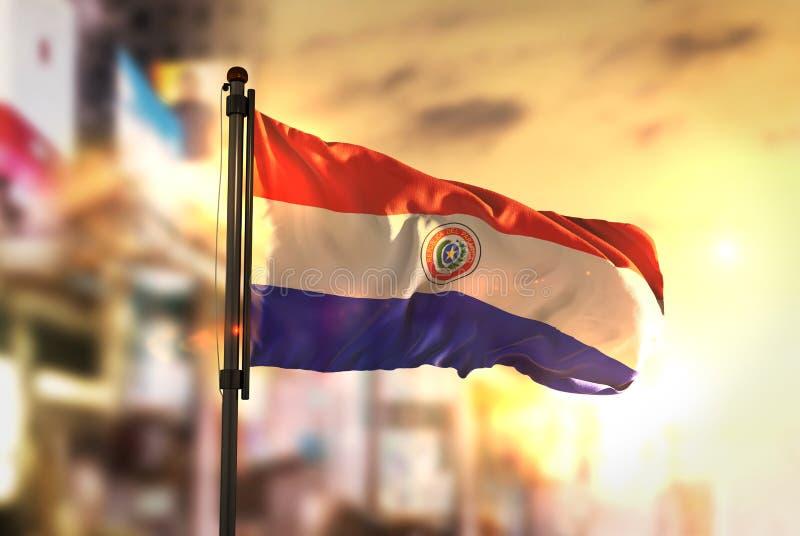 De Vlag van Paraguay tegen Stad Vage Achtergrond bij Zonsopgang Backlig royalty-vrije stock foto's