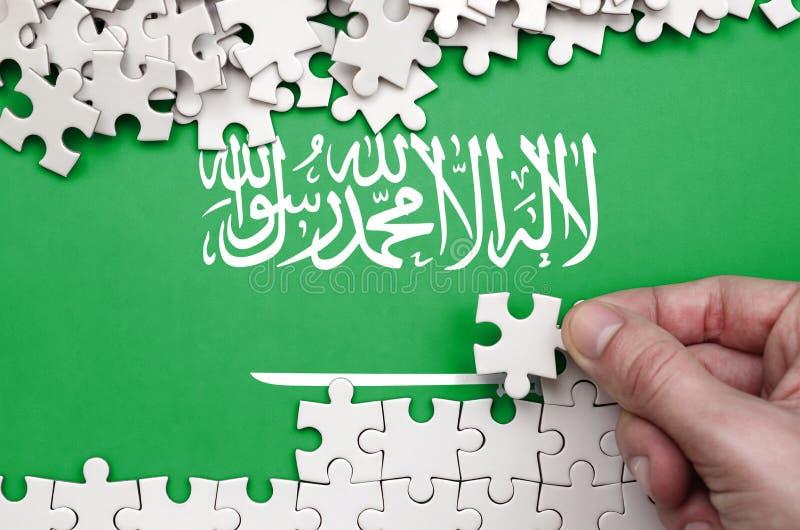 De vlag van Saudi-Arabië wordt afgeschilderd op een lijst waarop de menselijke hand een raadsel van witte kleur vouwt stock foto's