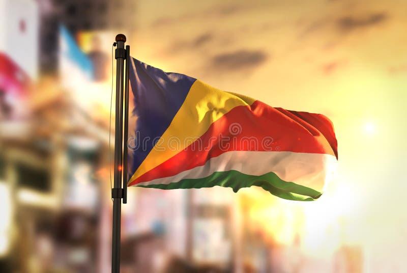 De Vlag van Seychellen tegen Stad Vage Achtergrond bij Zonsopgang Backl stock afbeeldingen