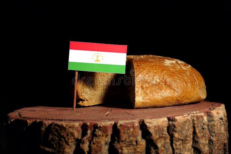 De vlag van Tadzjikistan op een stomp met brood stock foto