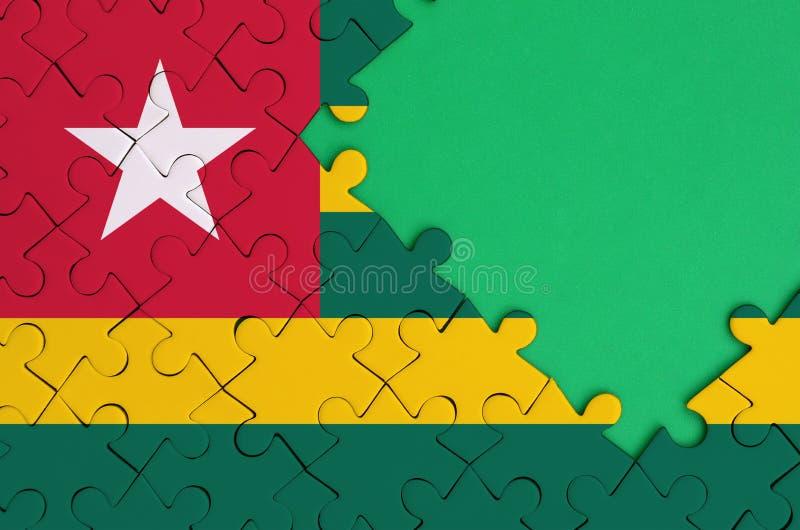 De vlag van Togo wordt afgeschilderd op een voltooide puzzel met vrije groene exemplaarruimte op de rechterkant stock foto