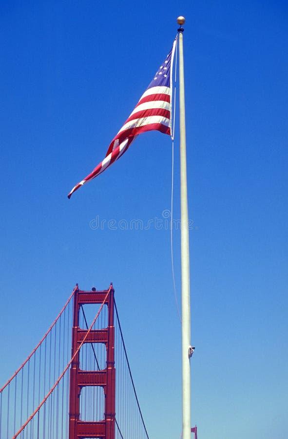 De vlag van de Verenigde Staten van Amerika of de Verenigde Staten op een vlaggenstok op de achtergrond van de Golden Gate Bridge royalty-vrije stock foto's