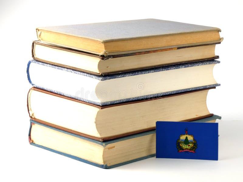 De vlag van Vermont met stapel van boeken op witte achtergrond royalty-vrije stock foto's