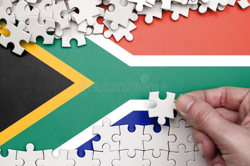 De vlag van Zuid-Afrika wordt afgeschilderd op een lijst waarop de menselijke hand een raadsel van witte kleur vouwt stock foto
