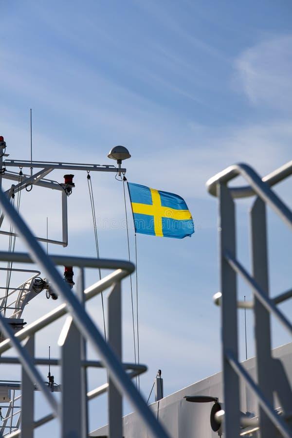 De vlag van Zweden vliegt in een zware wind op een cruiseschip De nadruk is op de vlag stock afbeelding