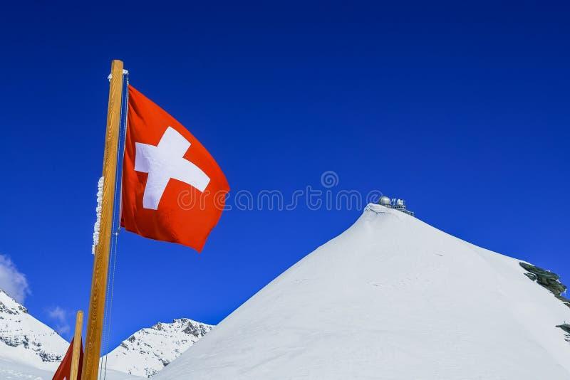 De vlag van Zwitserland en Sfinxwaarnemingscentrum boven jungfraujoch stock afbeelding