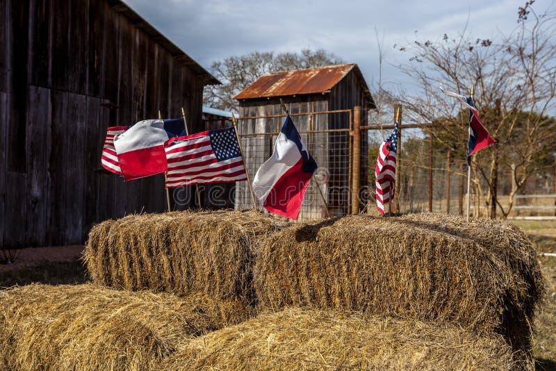 De vlaggen van Amerikaan en van Texas schikten op strobalen, de decoratie van de onafhankelijkheidsdag stock afbeelding