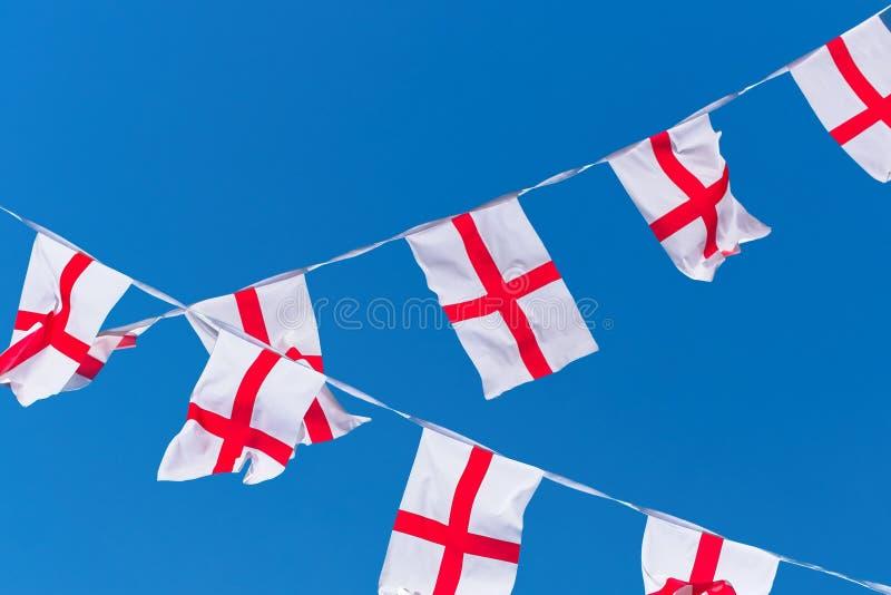 De vlaggen van Engeland/bunting tegen blauwe hemel stock foto's
