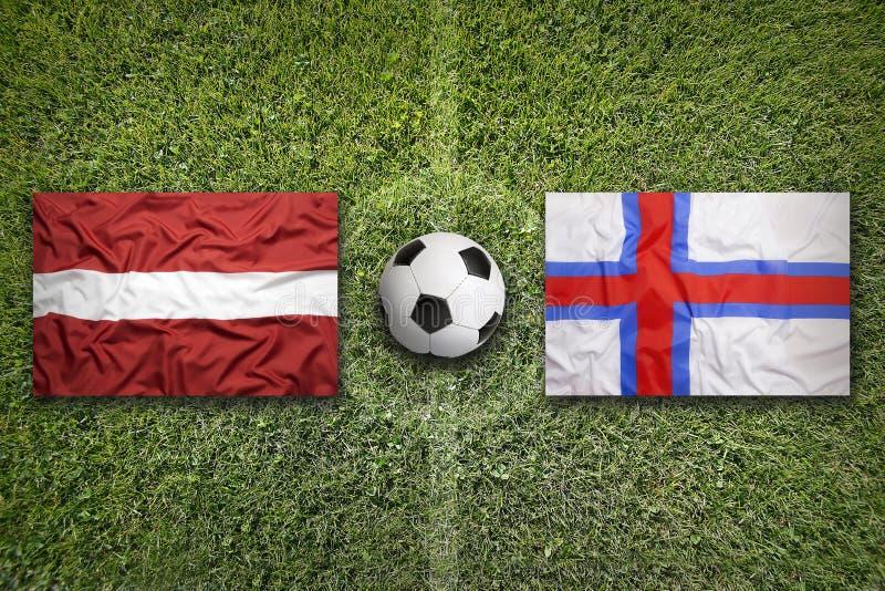 De vlaggen van Letland en van de Faeröer op voetbalgebied royalty-vrije stock fotografie